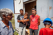 """Grandfather Rudolf (52, left) with his son Rudo who is holding his daughter. Beside Emil (20), all those are among six families which joined a pilot project constructing low-cost houses called """"From Shack into a 3E (Ecological and Energy Efficient) House"""",<br /> which was implemented in the village of Rankovce located about 30 km from Kosice in 2013. The pilot project took place in a marginalized Roma community - all the builders were<br /> unemployed Roma living with their families in difficult conditions."""