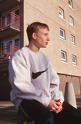 Teenage boy wearing sweatshirt sitting alone in front of block of flats,