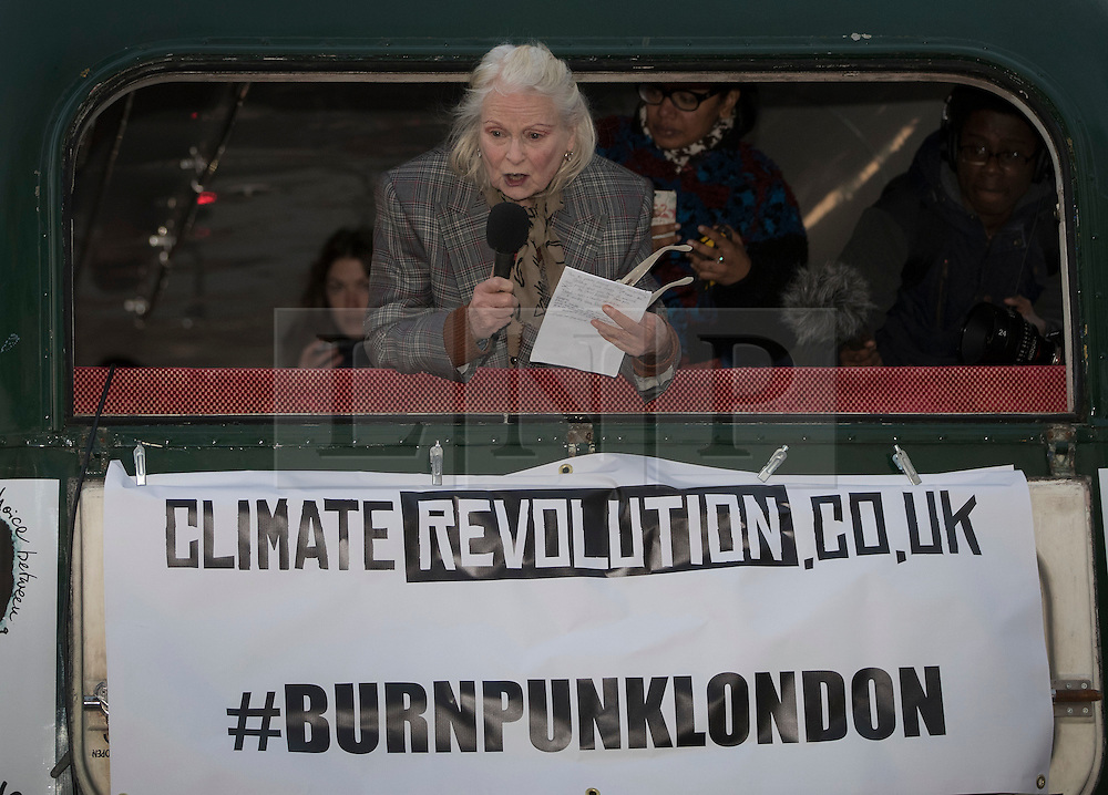 """© Licensed to London News Pictures. 26/11/2016. London, UK. Vivienne Westwood speaks from the back of a bus as Joe Corre (top right), the son of former Sex Pistol manager Malcolm McLaren and Vivienne Westwood burns his personal collection of Sex Pistols punk memorabilia on a boat in the Thames in Chelsea. Earlier this week Joe Corre said that punk has become nothing more than a """"McDonald's brand ... owned by the state, establishment and corporations"""". His collection is estimated to be worth £5 million. Photo credit: Peter Macdiarmid/LNP"""