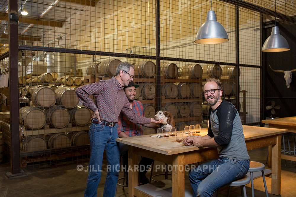 Tucson, AZ -- 09/28/2017<br /> <br /> (L- R) Hamilton Distillers founder Stephen Paul, assistant distiller Ram&oacute;n Olivas and his dog Scarlet and head distiller and maltser Nathan Thompson Avelino photographed in the tasting room at the Tucson distillery. <br /> <br /> Hamilton Distillers, makers of Whiskey Del Bac, is the first craft distillery in Southern Arizona since prohibition. The company produces three distinct single malt whiskeys, including Whiskey Del Bac Dorado which is malted over mesquite.<br /> <br /> The distillery offers tours and tastings on Saturdays at 3 p.m <br /> <br /> Photography by Jill Richards