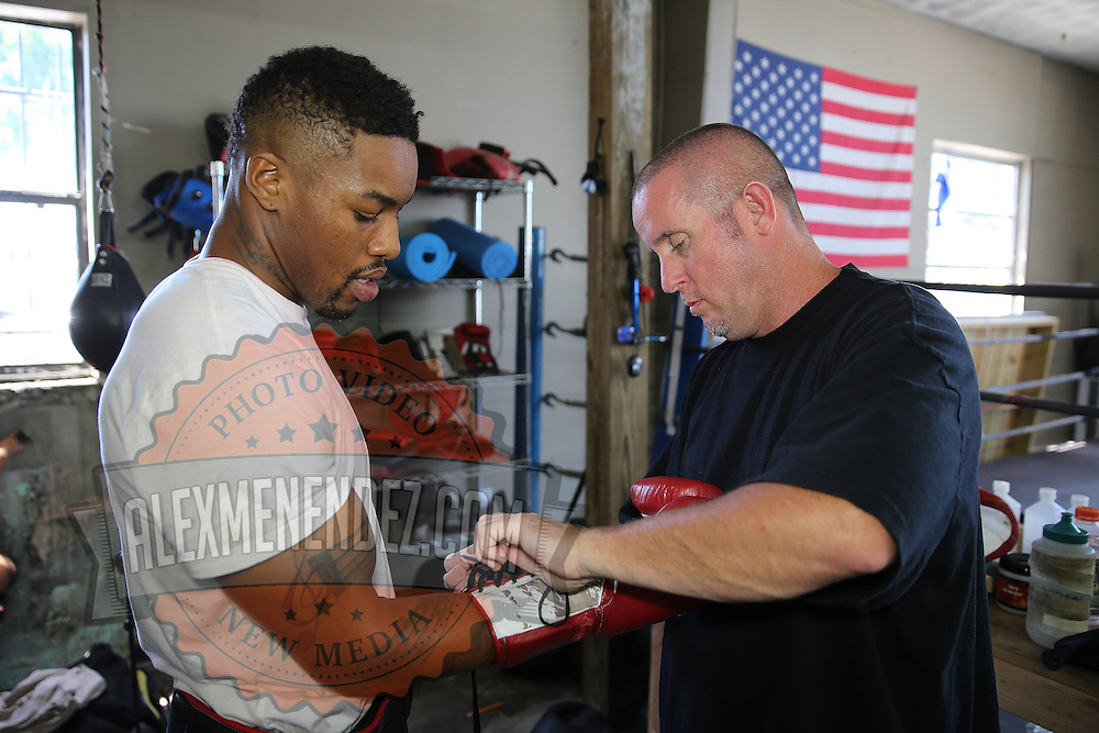 "WINTER HAVEN, FL - MAY 05: Boxer Willie Monroe Jr. (L) gets his gloves put on by trainer Tony Morgan before he works out at the Winter Haven Boxing Gym on May 5, 2015 in Winter Haven, Florida. Monroe will challenge middleweight world champion Gennady ""GGG"" Golovkin for the WBA world championship title in Los Angeles on May 16.  (Photo by Alex Menendez/Getty Images) *** Local Caption *** Willie Monroe Jr.; Tony Morgan"