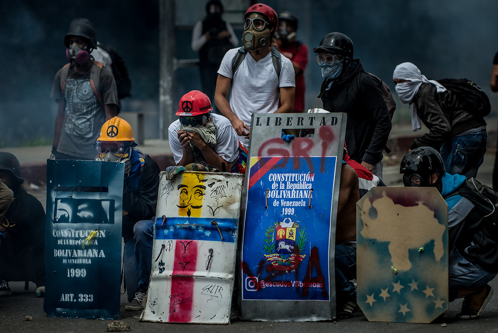 CARACAS, VENEZUELA - MAY 24, 2017:  Anti-government protesters take cover behind homemade shields during clashes with National Guard soldiers.  The streets of Caracas and other cities across Venezuela have been filled with tens of thousands of demonstrators for nearly 100 days of massive protests, held since April 1st. Protesters are enraged at the government for becoming an increasingly repressive, authoritarian regime that has delayed elections, used armed government loyalist to threaten dissidents, called for the Constitution to be re-written to favor them, jailed and tortured protesters and members of the political opposition, and whose corruption and failed economic policy has caused the current economic crisis that has led to widespread food and medicine shortages across the country.  Independent local media report nearly 100 people have been killed during protests and protest-related riots and looting.  The government currently only officially reports 75 deaths.  Over 2,000 people have been injured, and over 3,000 protesters have been detained by authorities.  PHOTO: Meridith Kohut
