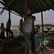 Young girls await customers at a riverboat landing outside the coal-powered electricty plant in Phai Lai, about 70 kilometers east of Hanoi, Vietnam, 14 September, 2007.