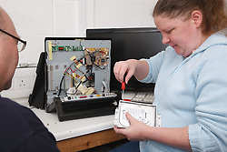 Woman with a mild learning disability working as a trainee computer technician, shown here changing hard drive, helped into employment by the Ready 4 Work team, Nottinghamshire County Council, with trainer