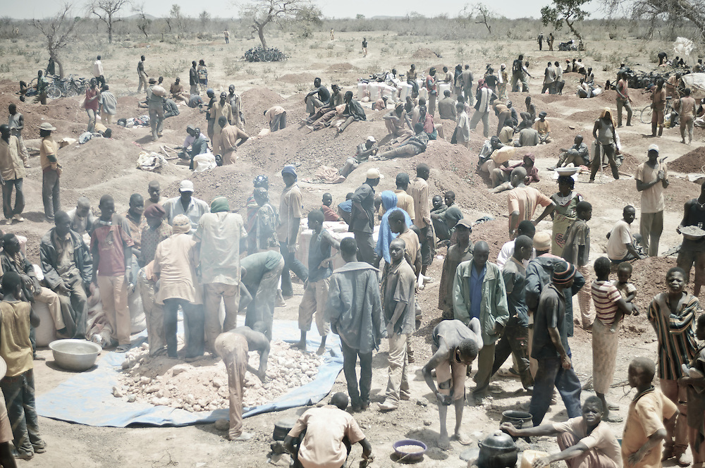 Stock photograph of an African gold rush in Burkina Faso with hundreds of African miners digging, sorting, and bagging gold ore.