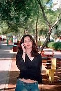 Woman on mobile phone strolling in Ben Gurion Boulevards, Tel Aviv, Israel