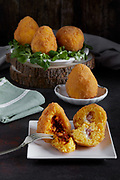 Arancini, traditional Italian food, mostly Sicilian,  stuffed with meat and peas ragu or, so-called butter, stuffed with ham and mozzarella cheese.