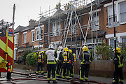London Fire Brigade (LFB) firefighters attend a roof fire in Herne Hill, south London.