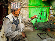 04 MARCH 2017 - KATHMANDU, NEPAL: A Nepali man spins wool in an IDP camp in the center of Kathmandu. The camp opened days after the April 2015 earthquake devastated Nepal, killing almost 9,000 people. At its peak, about 1,800 families lived in the camp. The camp is still open nearly two years after the earthquake, about 400 families currently live in the camp. Camp residents say the Kathmandu municipal government is trying to close the camp and is encouraging residents to find new housing. They said the government is cutting off services to the camp and last week stopped the free distribution of water, although water can be purchased for delivery. Most of the people in the camp came to Kathmandu from rural villages in the mountains in the weeks after the earthquake. Many of the residents of the camp, technically homeless, have found work in Kathmandu's bustling construction industry, rebuilding homes destroyed in the earthquake.       PHOTO BY JACK KURTZ