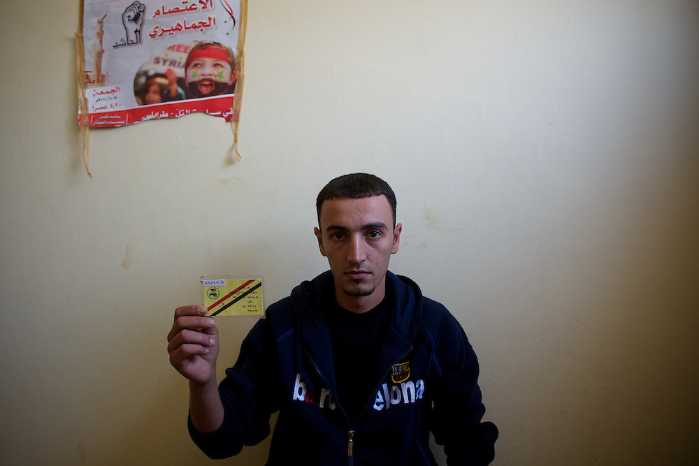Omar Mora'ay, a 26 year old defected soldier from the Syrian national Army, shows is military identification card at a refugee center in Wadi Khaled, northern Lebanon.