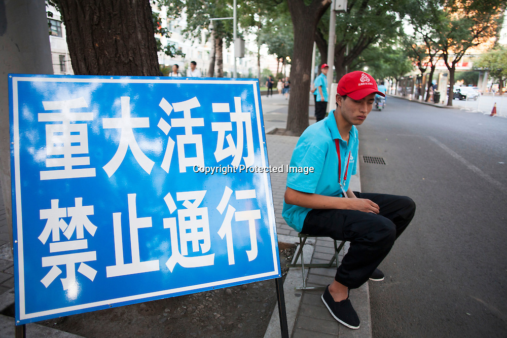 """BEIJING, SEPT.9,2015 : """"volunteers"""" show p in the late afternoon of Sept. 2 to make sure the  sidewalks and streets are gradually emptied for the celebrations to  commemorate the 70th anniversary of the end of World War II.<br /> The note in Chinese translates as """" big event, forbidden to pass """""""