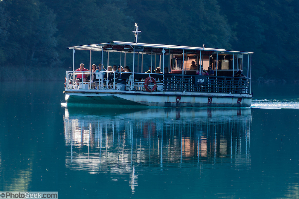 Visitors ride a shuttle boat across Lake Kozjak in Plitvice Lakes National Park (Nacionalni park Plitvicka jezera, in Croatia, Europe). Lake Kozjak connects the Lower Lakes (Donja Jezera) with the Upper Lakes (Gornja Jezera). The park was founded in 1949 and is honored by UNESCO as World Heritage Site. Waters flowing over limestone, dolomite, and chalk in this karstic landscape have, over thousands of years, deposited travertine barriers, creating natural dams, beautiful emerald lakes and waterfalls. Warming conditions after the last Ice Age (less than 12,000 years ago) allowed the natural dams to form from tufa (calcium carbonate) and chalk depositing in layers, bound by plants. Plitvicka Jezera is a municipality of Lika-Senj County, in the Republic of Croatia.