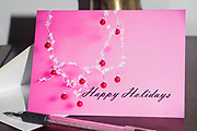 Photo holiday greeting card with red holiday ornaments hanging from a snow flake garland against a bright pink background. Modern Holiday Card, Happy Holidays greeting card, Holiday Card, Christmas Card, card, paper goods, Santa Monica, Southern CA.