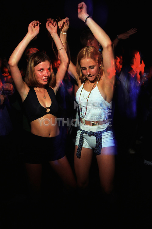 Two girls dancing with their arms up at a rave, United Dance Stevenage. 27th June 1997