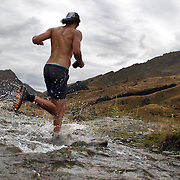 A runner crosses Moke Creek on the Ben Lomond High Country Station on his way to winning the Pure South Shotover Moonlight Mountain Marathon and trail runs. Moke Lake, Queenstown, New Zealand. 4th February 2012. Photo Tim Clayton