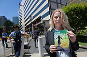 "Rape Survivor and activist, Catherine ""Jane"" Fisher writes a message to Ambassador Caroline Kennedy in her book before presenting it to a member of staff at the American Embassy in Tokyo, Japan, Friday July 11th 2014. Ms Fisher was raped near Yokusuka US Navel Base in Kanagawa in 2002 and has been campaign for the rights of rape victims in Japan since, after finding the US Military and Japanese police obstructive and uninterested in bringing her attacker to justice."