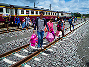 05 JULY 2017 - ARYANAPHRATET, THAILAND: Cambodian migrant workers walk through the train yard in Aranyaphratet, Thailand, on the Thai-Cambodia border. The migrant workers are leaving Thailand after the Thai government proposed new rules for foreign workers. The new rules include fines of between 400,000 and 800,00 Thai Baht ($12,000 - $24,000 US) and jail sentences of up to five years for illegal workers and people who hire illegal workers. Hundreds of companies fired their Cambodian and Burmese workers and tens of thousands of workers left Thailand to return to their countries of origin. Employers and human rights activists complained about the severity of the punishment and sudden implementation of the rules. On Tuesday, 4 July, the Thai government suspended the new rules for 180 days and the Cambodian and Myanmar governments urged their citizens to stay in Thailand, but the exodus of workers continued through Wednesday.    PHOTO BY JACK KURTZ