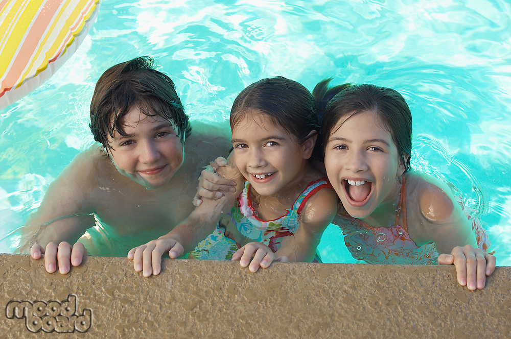 Two girls and boy in swimming pool, portrait