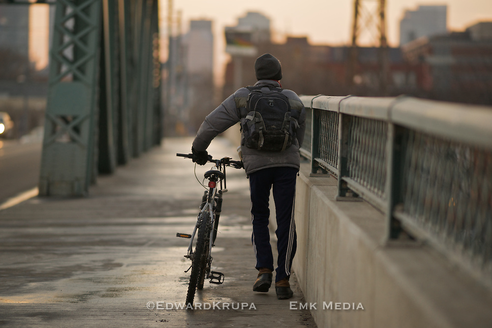 Man walking his bike over a bridge at sunset. Queen St.E., Toronto.