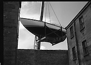 "The ""Asgard "" at Kilmainham Jail..1979..01.04.1979..04.01.1979..1st April 1979..The historic yacht ""Asgard"" owned by Erskine Childers was brought to Kilmainham Jail,Dublin. The vessel had to be hoisted ,by crane,over the outer wall of the jail. It was placed as part of a future exhibition to be set up by The National Museum..Image of the crane slowly lifting the yacht up over the jail wall."