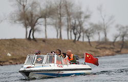 A Chinese tourist boat travels along the North Korean bank of the Yalu River near the town of Sinuiji across the Chinese city of Dandong, Liaoning Province, China on 06 April 2013. North Korean leader Kim Jong-un has ordered the country's military to increase artillery production, a televised report out of Pyongyang showed 06 April.
