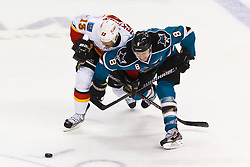 Jan 17, 2012; San Jose, CA, USA; Calgary Flames center Olli Jokinen (13) and San Jose Sharks center Joe Pavelski (8) fight for a loose puck during the third period at HP Pavilion. San Jose defeated Calgary 2-1 in shootouts. Mandatory Credit: Jason O. Watson-US PRESSWIRE