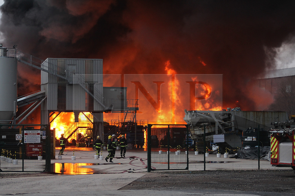 "© Licensed to London News Pictures . 15/03/2015 . Salford , UK . Fire crew at the scene . Roads are closed and people have been evacuated as a large fire burns at a unit within "" Junction Eco-Park "" in Clifton , Greater Manchester , this evening (Sunday 15th March 2015) . The smoke and flames can be seen for many miles . Forty fire fighters are at the scene working to control the blaze . Photo credit : LNP"