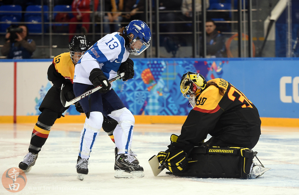 Feb 16, 2014; Sochi, RUSSIA; Germany goalkeeper Jennifer Harss (30) covers the puck as Finland forward Rikka Valila (13) looks for the rebound in the women's ice hockey classifications round during the Sochi 2014 Olympic Winter Games at Shayba Arena.