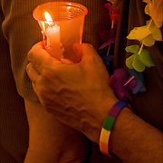 AIDS Candlelight Vigil, remembrance of love ones who died of AIDS.<br /> Closeup of gay male holding candle, wearing rainbow bracelet and rainbow flowers.