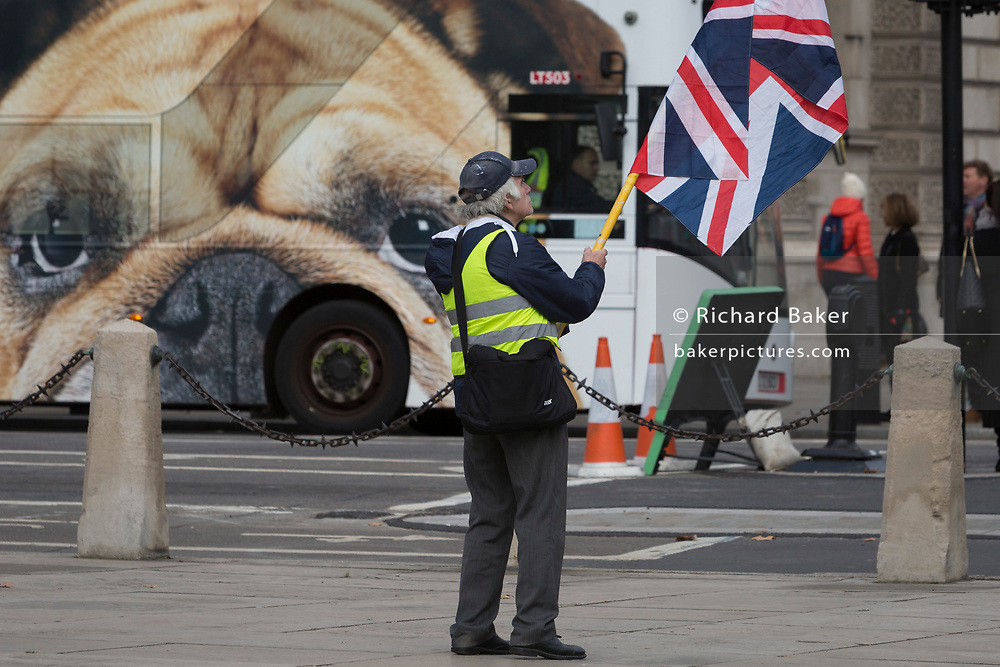 A far-right 'yellow vest' protests as a British Bulldog bus ad drives through Parliament Square opposite the UK Parliament in a week that Prime Minister Theresa May once again asks for MPs to back her Brexit deal, on 14th January 2019, in Westminster, London, England.