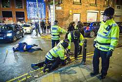© Licensed to London News Pictures . 01/01/2016 . Manchester , UK . Police detain a man whilst another lies collapsed in the road . Revellers in Manchester on a New Year night out at the clubs around the city centre's Printworks venue . Photo credit : Joel Goodman/LNP