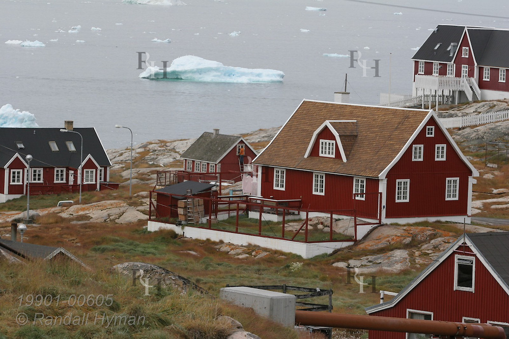 Danish-style wooden buildings perch along rocky shore overlooking Disko Bay iceberg chunks at Ilulissat, third largest town in Greenland.
