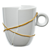 rubber string holding together a in two broken porcelain cup