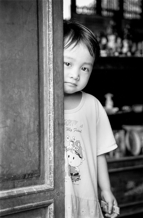 "A young child shyly poses for the shot, hiding behind a door, in the ancient citadel of Hue in central Vietnam. The T-shirt says ""My friend""."