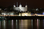 A photo of the Tower of London, taken from the banks of the River Thames at night. Her Majesty's Royal Palace and Fortress is a historic castle located in the Borough of Tower Hamlets and was built by William the Conqueror in 1078.