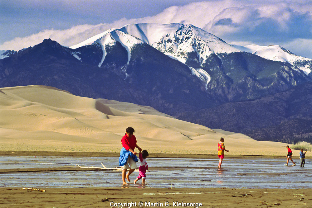 Tourist crossing the intermittent flowing Medano Creek.  Great Sand Dunes National Park, Colorado, USA.