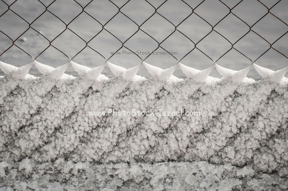 Israel, Dead Sea, salt crystalization on a fence caused by water evaporation.