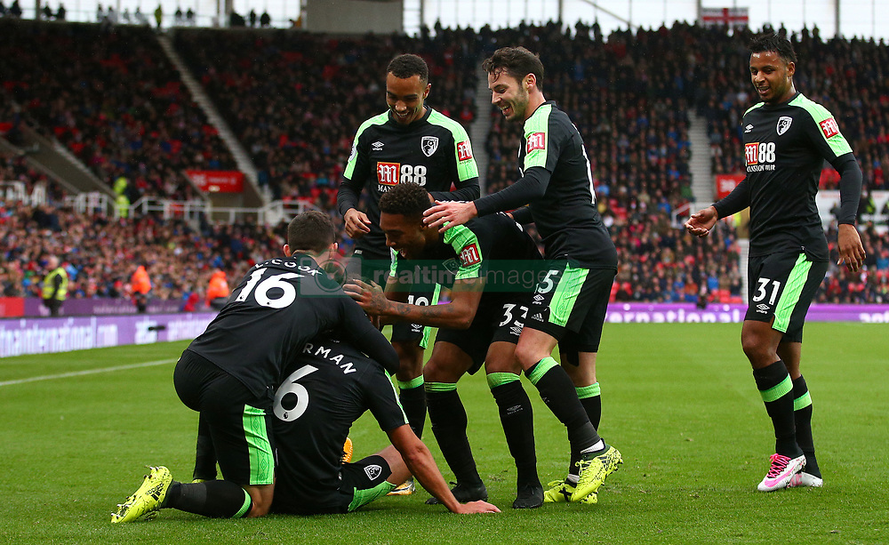AFC Bournemouth's Andrew Surman is mobbed by his team-mates after scoring his side's first goal during the Premier League match at the bet365 Stadium, Stoke-on-Trent.