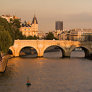 People gather at sunset near the Pont Neuf bridge across the Seine River, Paris France<br />