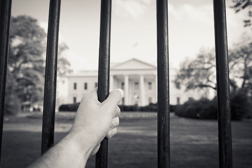 A hand gripping the fence outside The White House in Washington, DC, USA.