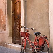 Red bicycle , weathered wall and wooden door Chioggia Italy