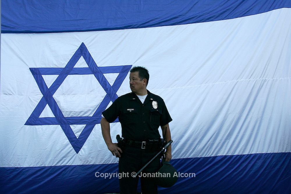 An LAPD officer stands by an Israeli flag at a  pro Israel rally held in front of the Israeli Consulate in Los Angeles. Wilshire Blvd was closed down for the event and there was a heavy police presence at the rally which was held in response to the political firestorm that continues a week after Israeli commandos killed nine protesters who defied a naval blockade of Gaza and attacked the soldiers.
