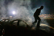 Arkansas Democrat-Gazette/BENJAMIN KRAIN --9/21/2013--<br /> A driver and climbs out of his window after his vehicle is immobilized during the Des Arc Demolition Derby