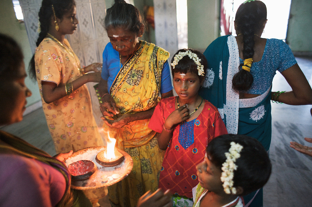 Anjalakshi, age 9, (in red) visits a temple in Pudupettai to mark the Hindu festival of Diwali. She is accompanied by their sisters and maternal grandmother Chitra (yellow sari). The Krishnamurthy sisters spent the Diwali weekend visiting relatives while staying with their father in their home town of Puddupettai. <br />