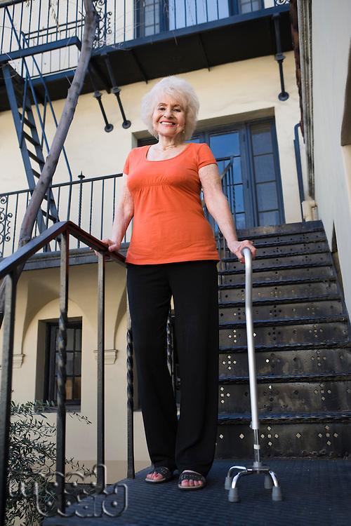 Woman with walking cane outside house