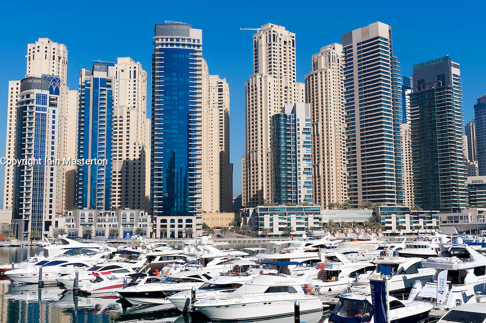 View of high-rise modern building towers and yachts in Marina at New Dubai in United Arab Emirates