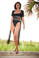 Picture of a swimsuit model, dressed in a black swimsuit with a sheer center pannel and a sheer black coverup.