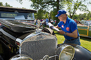 Old Westbury, New York, U.S. - June 1, 2014 -  A judge evaluates a red and black 1927 La Salle 303 Roadster, owned by JOHN MICCICHE of SMITHTOWN, which is an entry at the Antique and Collectible Auto Show held on the historic grounds of elegant Old Westbury Gardens in Long Island, and sponsored by Greater New York Region AACA Antique Automobile Club of America.