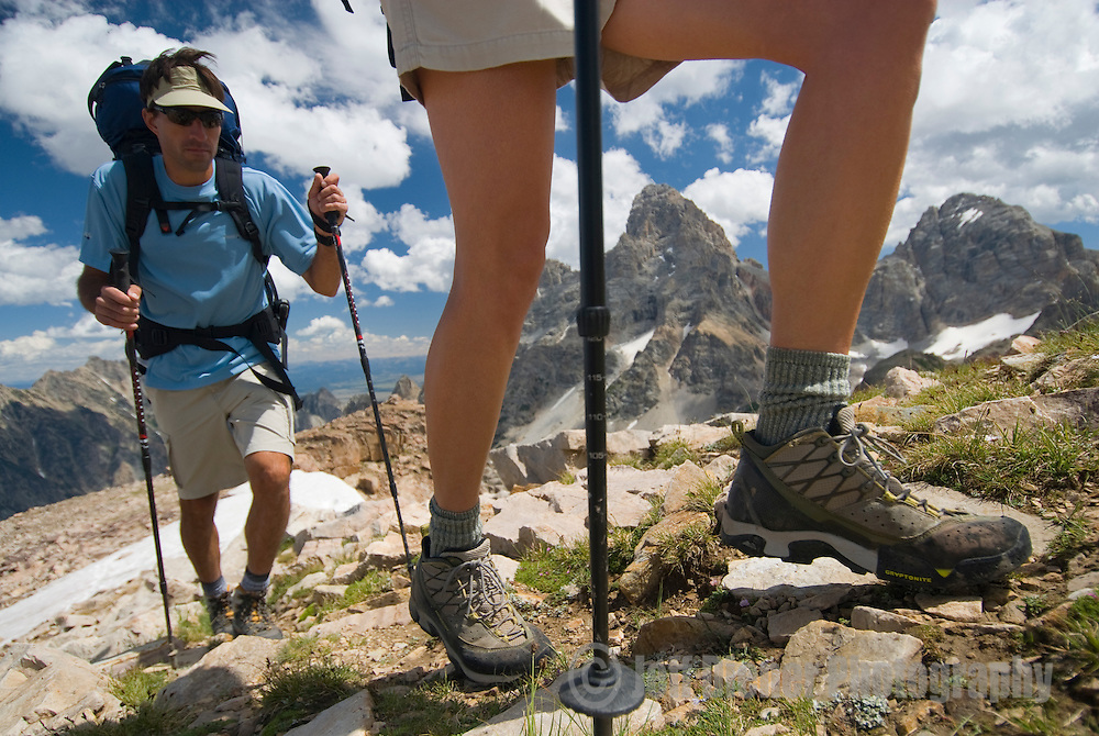 A pair of hikers traverse the high alpine of the Teton Range, Wyoming.