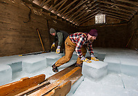 Asa Berg and Jack Sengstaker guide sliding ice blocks into place inside the Deephaven Ice House on Wednesday during the annual Rockywald/Deephaven Camps Ice Harvest.  (Karen Bobotas/for the Laconia Daily Sun)